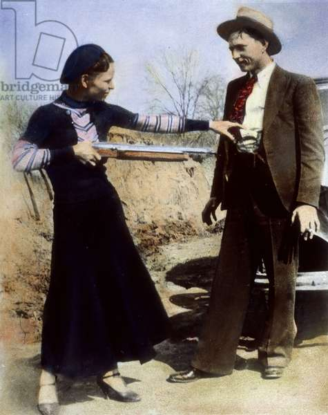 BONNIE AND CLYDE, 1933 American criminal Bonnie Parker (1911-1934) playing at holding up her partner, Clyde Barrow (1909-1934). Oil over a photograph, 1933.