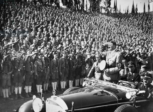 ADOLF HITLER (1889-1945) Chancellor of Germany, 1933-45. Hitler saluting the Hitler Youth at a Nazi Party rally, 1934.