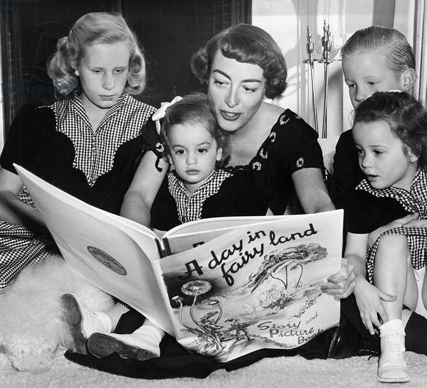JOAN CRAWFORD (1908-1973). American actress. Crawford reading a book to her four children. Photograph, c.1950.