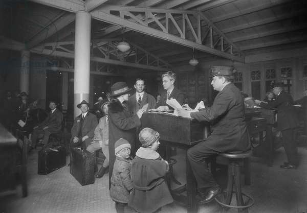 IMMIGRANTS: ELLIS ISLAND Immigration officials examining an immigrant family. Photograph, by Lewis Hine, c.1917.