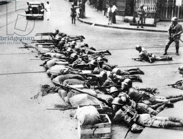 CHINA: JAPANESE INVASION Japanese marines fighting in the streets of Shanghai behind a sandbag barricade, September 1937.