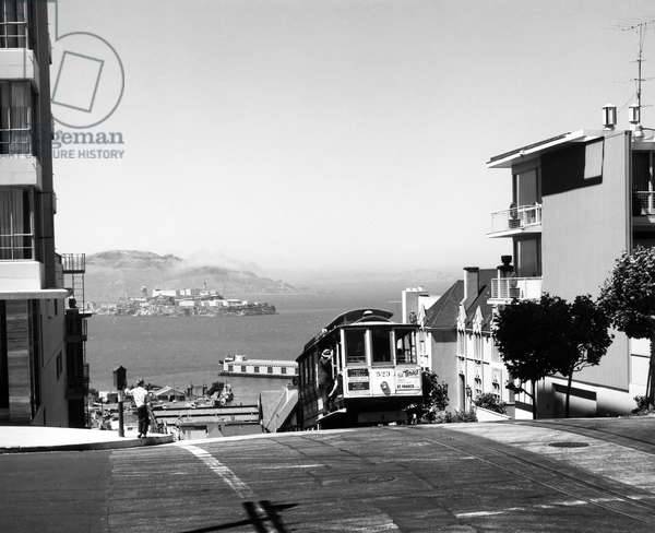 SAN FRANCISCO: CABLE CAR A cable car mounts Hyde Street in San Francisco, California. Alcatraz Island can be seen in the background. Photographed c.1950.