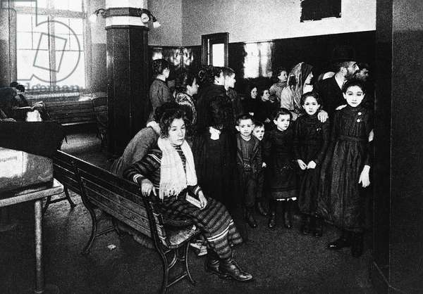 ELLIS ISLAND: IMMIGRANTS Immigrants waiting in the detention room at Ellis Island, New York City. Illustration after a photograph, c.1902.
