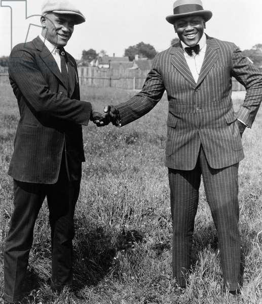 JACK JOHNSON (1878-1946) American heavyweight pugilist. Johnson, right, photographed shaking hands with fellow boxer James 'Tut' Jackson (1900-1960), c.1922.