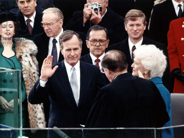 GEORGE H.W. BUSH (1924- ) 41st President of the United States. Being administered the Oath of Office by Chief Justice William Rehnquist, with Vice President Dan Quayle and First Lady Barbara Bush looking on. Photograph, 20 January 1989.