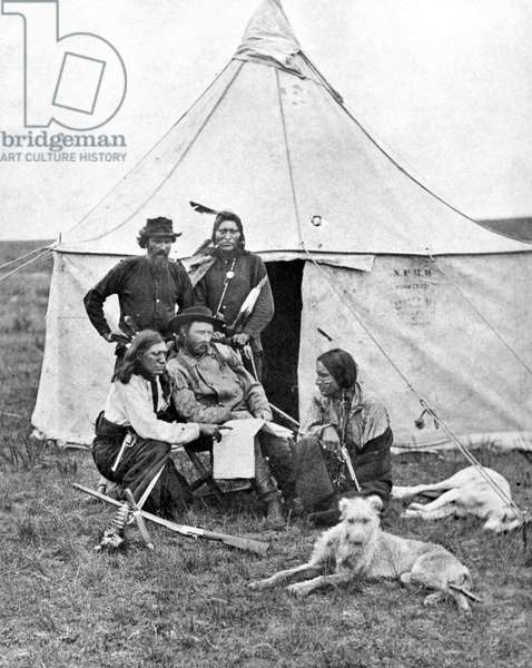 GEORGE ARMSTRONG CUSTER (1839-1876). American army officer. Photographed with scouts during the Yellowstone Expedition, 1873.