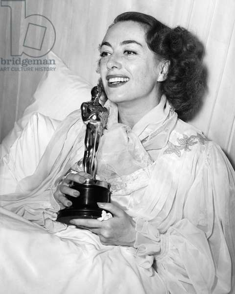 JOAN CRAWFORD (1908-1973) American actress. Crawford accepting her Oscar for Best Actress for her role in 'Mildred Pierce.' Crawford was sick and unable to attend the ceremony. Photograph, 1946.