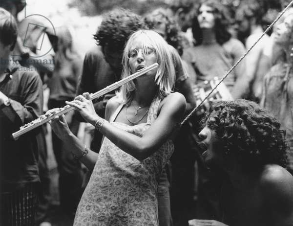 HIPPIE MOVEMENT, 1969 A woman plays the flute with other musicians at the Woodstock music festival in New York State.