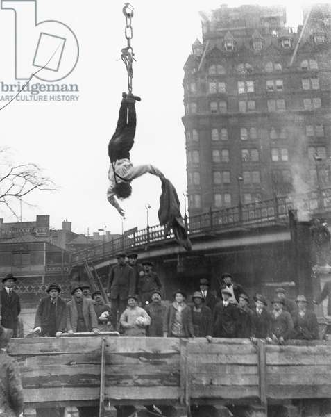 HARRY HOUDINI (1874-1926) American magician. Houdini escaping from his straitjacket while suspended during a midair stunt in 1916.