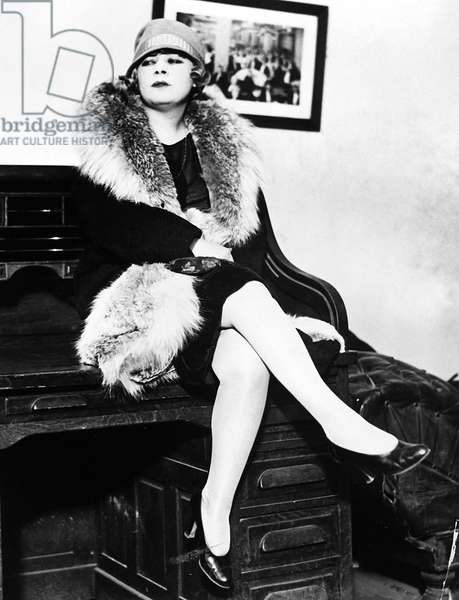 MAE WEST (1892-1980) American actress. Mae West seated on a desk during the obscenity trial for her play, 'Sex,' in 1928.