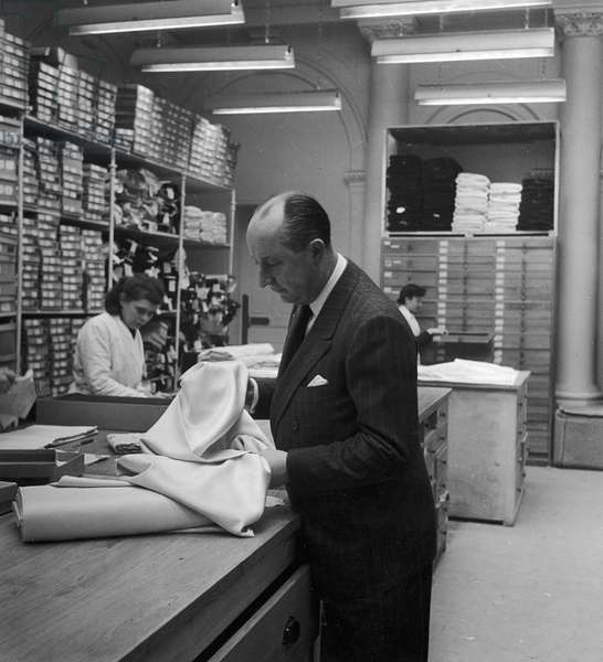 CHRISTIAN DIOR (1905-1957) French fashion designer. Dior inspecting fabric at a store, 1940s or 1950s.