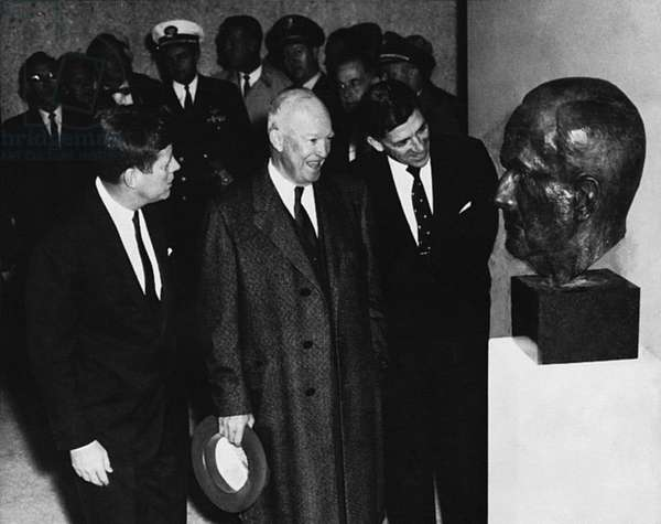 KENNEDY AND EISENHOWER John F. Kennedy and Dwight D. Eisenhower looking at a bust of Eisenhower. Photograph, c.1961.
