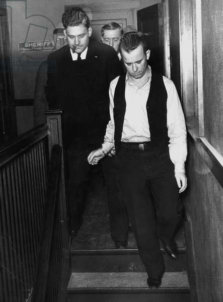 JOHN DILLINGER (1903-1934) American bank robber, 1934. Dillinger (wearing open vest) being led from jail to a courtroom at Crown Point, Indiana, on 9 February 1934, for arraignment on the charge of killing a policeman in East Chicago, Indiana.