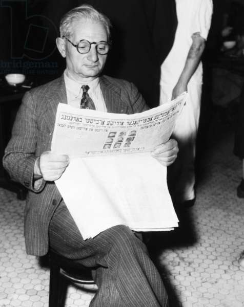 ELLIS ISLAND: REFUGEE Wolf Rubenstein reading a Jewish newspaper at Ellis Island, waiting with 487 other displaced Jews en route to Israel from Shanghai, China. Photograph, 1949.