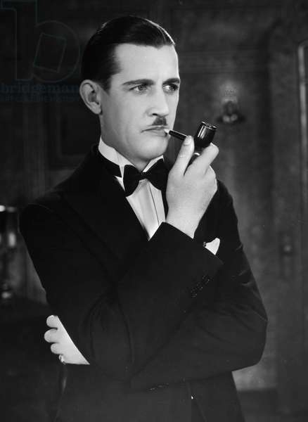 SILENT FILM STILL: SMOKING. Charley Chase (1893-1940) with pipe, 1928.