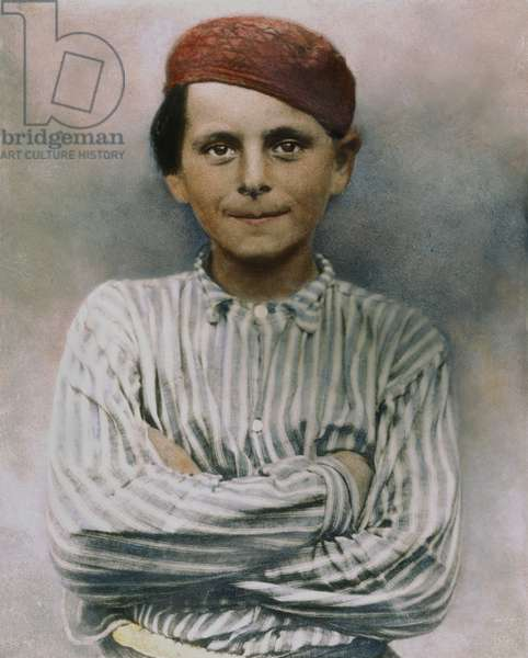 IMMIGRANT BOY, c.1900 At Ellis Island, New York City: oil over a photograph, c.1900.