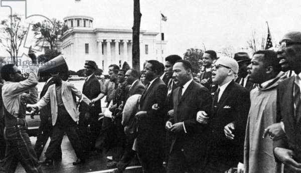 MARTIN LUTHER KING, JR (1929-1968). American clergyman and reformer. Dr. King (fourth from right) leading the march from Selma on the state capitol at Montgomery, Alabama, 25 March 1965.