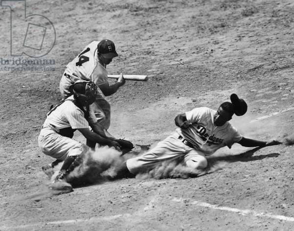 JACKIE ROBINSON (1919-1972) John Roosevelt Robinson, known as Jackie. American baseball player. As a member of the Brooklyn Dodgers, stealing home under the tag of catcher Andy Seminick in a game against the Philadelphia Phillies, at Shibe Park, Philadelphia, Pennsylvania, 2 July 1950. The Dodgers batter is Gil Hodges.