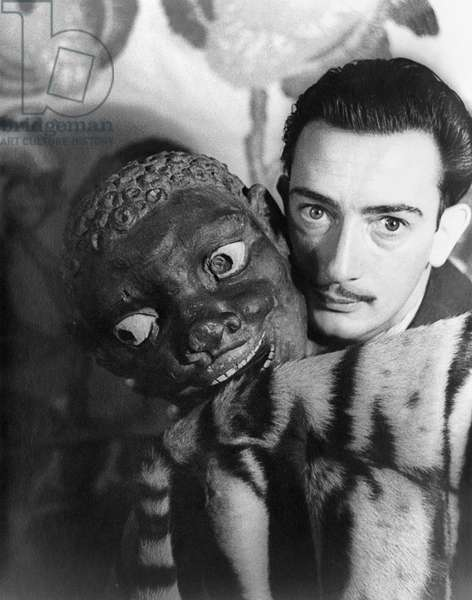 SALVADOR DALI (1904-1989) Spanish painter. Photographed by Carl Van Vechten, with a carved mask, 1939.