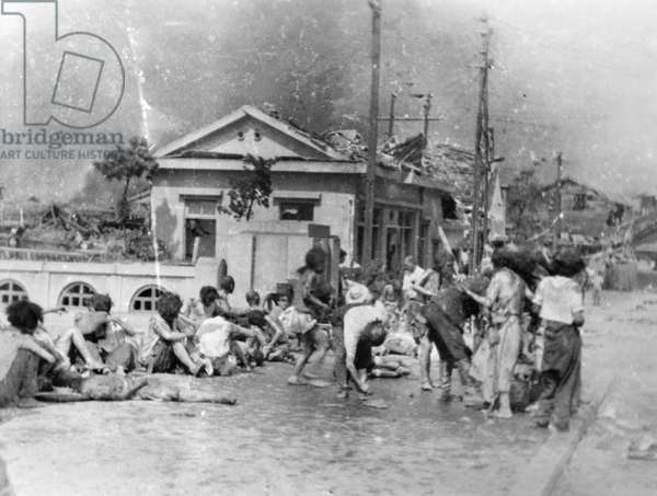 WORLD WAR II: HIROSHIMA Victims of the first atomic bomb wait to receive medical aid in the southern part of the shattered city of Hiroshima, 6 August 1945.