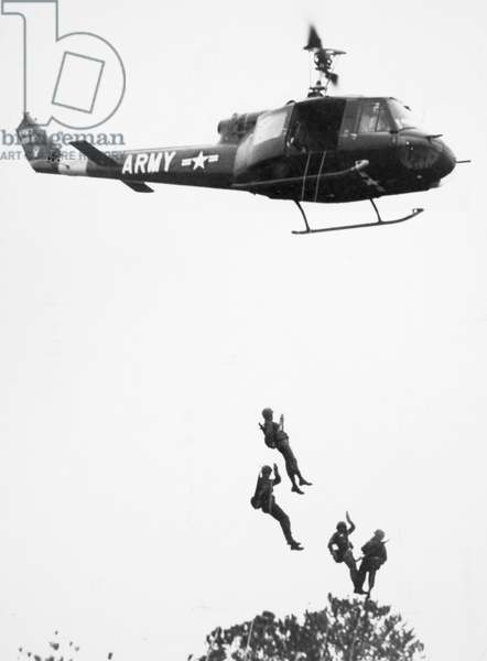 VIETNAM WAR: HELICOPTER U.S. troopers rappel from a helicopter in South Vietnam. Photograph, mid to late 1960s.