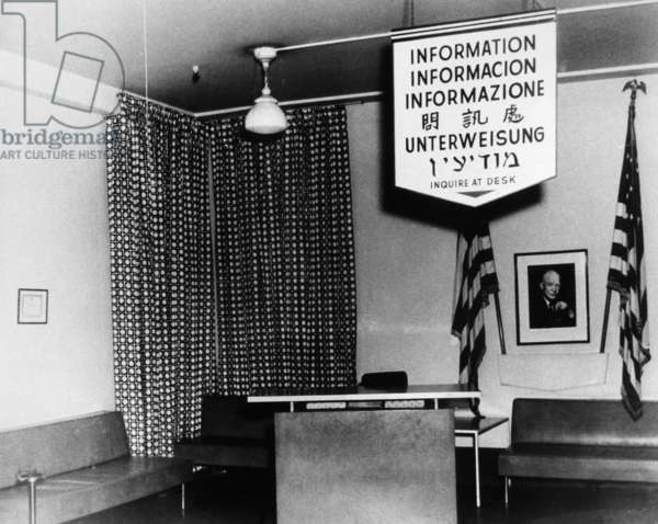ELLIS ISLAND, c.1953 An information desk with a multi-lingual sign at Ellis Island. Photograph, c.1953.