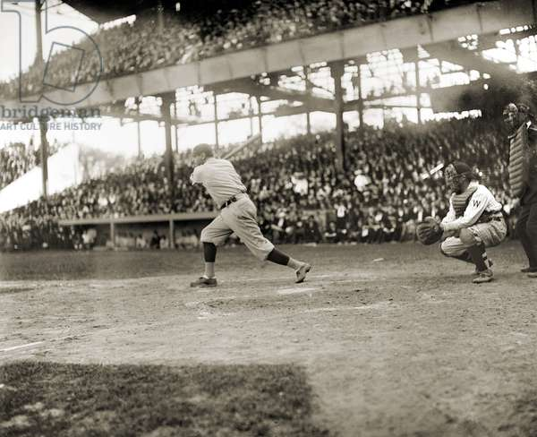 GEORGE H. RUTH (1895-1948) Known as Babe Ruth. Ruth swinging at a pitch during a game against the Washington Senators, c.1921.