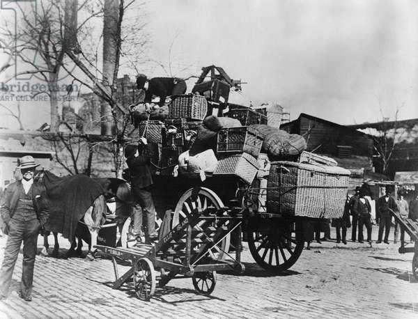 ELLIS ISLAND, c.1910 Men loading immigrants' baggage on to a wagon at Ellis Island.