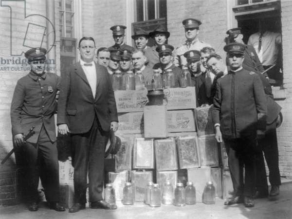 LIQUOR RAID, 1923 Group of policemen posed with cases of moonshine in Washington, D.C., 23 September 1923.