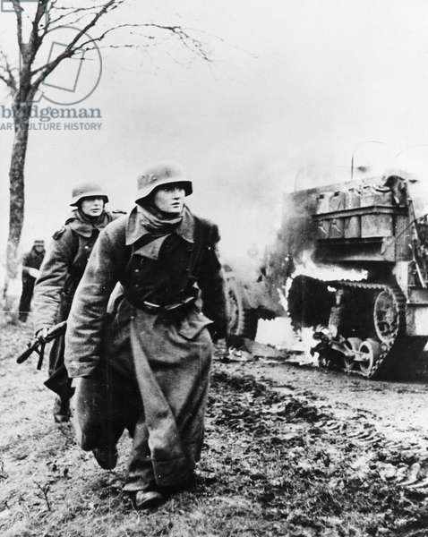 BATTLE OF THE BULGE, c.1944 German troops passing by a burning US Army vehicle as the German infantry advanced during the Battle of the Bulge, possibly in Poteau, Belgium. Photograph, 1944 or 1945.