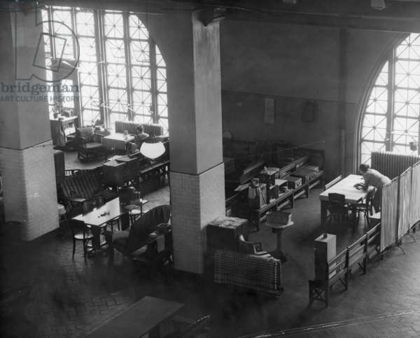 ELLIS ISLAND, c.1943 A gathering area (in the former registry room) for families detained as 'enemy aliens' on Ellis Island during World War II. Photograph, c.1943.