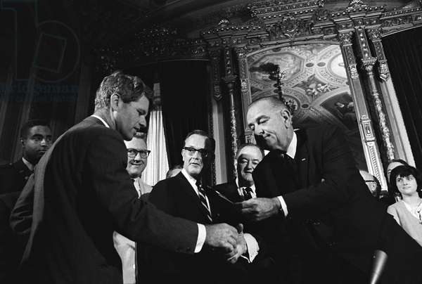 VOTING RIGHTS ACT, 1965 President Lyndon B. Johnson handing Senator Robert F. Kennedy a pen from the signing of the Voting Rights Act. Photograph by Yoichi Okamoto, 6 August 1965.