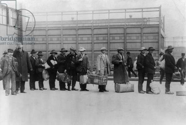 ELLIS ISLAND, c.1911 Immigrant men arriving at Ellis Island with their belongings, from the ship 'Princess Irene,' c.1911.