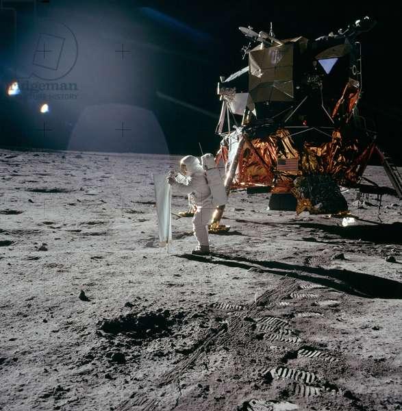APOLLO 11, 1969 Edwin 'Buzz' Aldrin erecting a solar wind collector experiment near the Apollo 11 Lunar Module. Photograph, 20 July 1969.