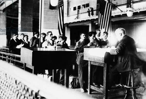 ELLIS ISLAND: REGISTRY ROOM Newly arrived immigrants in the registry room at Ellis Island, New York City. Photograph, May 1920.