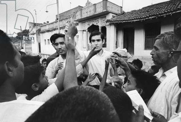 PEACE CORPS: INDIA Peace Corps volunteer Laurence Miller distributing family planning information in Monghyr, India. Photograph, c.1965.