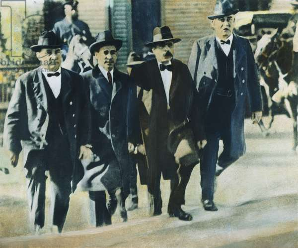 SACCO AND VANZETTI, 1921 Flanked by Massachusetts deputy sheriffs, Nicola Sacco (second from left) and Bartolomeo Vannzetti enter the Norfolk County courthouse at Dedham, Massachusetts, 1921. Oil over photograph.