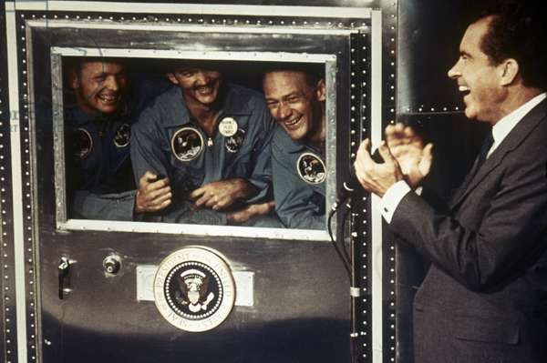SPACE: APOLLO 11 President Richard M. Nixon applauds astronauts Neil Armstrong, Michael Collins, and Edwin 'Buzz' Aldrin in the quarantine trailer, 1969.