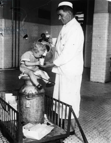 ELLIS ISLAND: MILKMAN, 1925 A milkman pouring milk for a young French immigrant detained at Ellis Island, awaiting deportation. Photograph, 1925.
