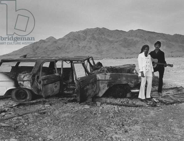 IKE AND TINA TURNER, 1969 American musicians Ike and Tina Turner pose beside a burned-out station wagon in the desert outside Las Vegas in 1969.