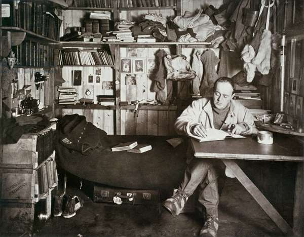 ROBERT FALCON SCOTT (1868-1912). English Antarctic explorer. Scott writing up his journal in his cabin in the Antarctic. Photographed by Herbert Ponting, 1911.