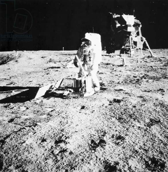 APOLLO 11, 1969 Astronaut Edwin 'Buzz' Aldrin deploying the Passive Seismic Experiments Package (PSEP) on the surface of the moon during the Apollo 11 mission, 20 July 1969. Between Aldrin and the lunar module, at left, is the already-deployed Laser Ranging Retro-Reflector (LR3). Photographed by astronaut Neil Armstrong.