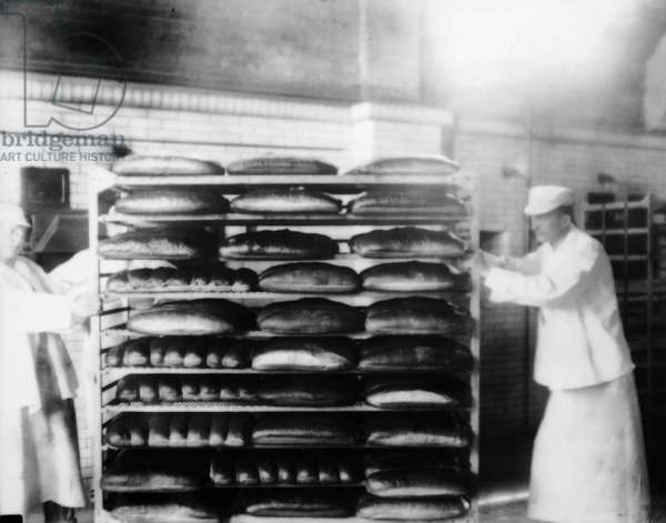 ELLIS ISLAND, 1920s Bakers moving a stack of freshly baked bread, 1920s.