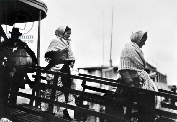 ELLIS ISLAND: IMMIGRANTS Immigrants walking down the gangplank from a ferry boat at Ellis Island, New York City. Photographed by Lewis Hine, 1905.