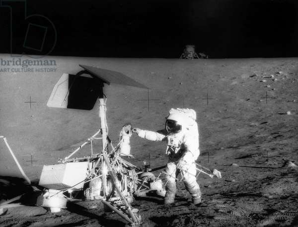 APOLLO 12, 1969 After landing in the Ocean of Storms in the Apollo 12 lunar module 'Intrepid' (rear), astronaut Charles Conrad, Jr. examines the television camera of the unmanned Surveyor III spacecraft, 20 November 1969. Surveyor III had soft-landed there more than two years earlier, in April 1967. Photographed by astronaut Alan Bean.