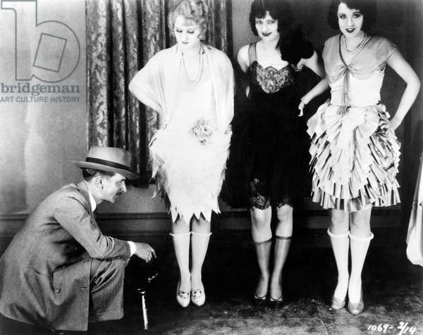 WOMEN'S FASHION: 1920S These three flappers of the 20's stylishly expose their knees by rolling down their silk stockings.