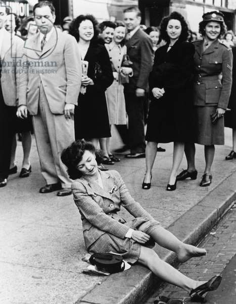 NYLON STOCKINGS, 1945 A young woman trying on nylon stockings on the street, after stockings went on sale again after World War II. Photograph, 1945.
