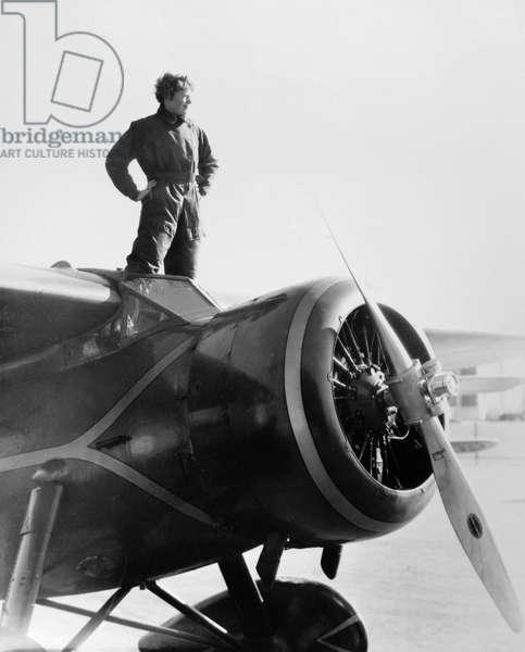 AMELIA EARHART (1897-1937) American aviator. Photographed with her Lockheed Vega monoplane, c.1932.