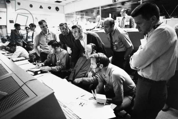 APOLLO 13: MISSION CONTROL Astronauts and flight controllers in the Mission Control Room at the Manned Spacecraft Center during the Apollo 13 mission. Left to right: (sitting) Raymond Teague, Edgar Mitchell, Alan Shepard Jr.; (standing) Anthony England, Joe Engle, Eugene Cernan, Ronald Evans, M.P Frank. Photograph, 1970.