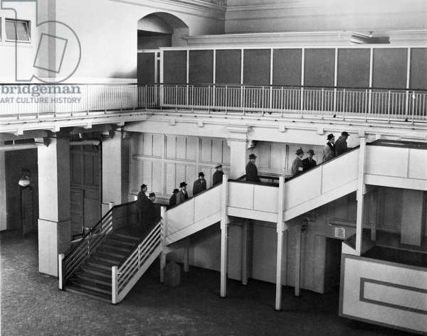 ELLIS ISLAND, 1958 Prospective buyers of Ellis Island ascending a staircase in the former registry room. Photograph, 1958.